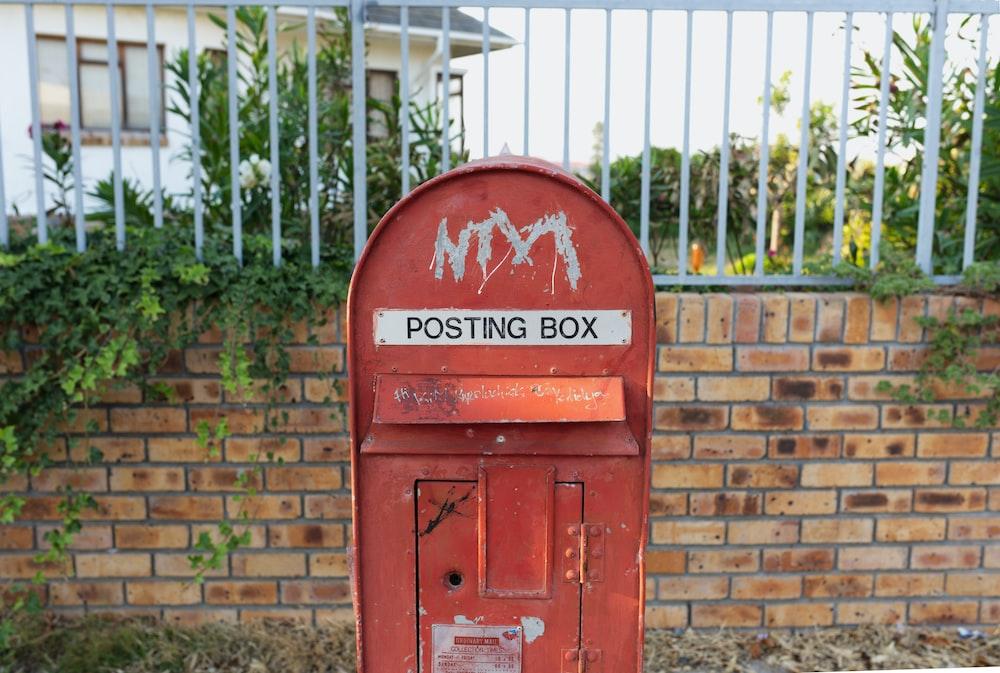 red mail box near brown brick wall