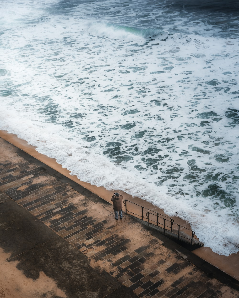 person standing on brown wooden dock near ocean waves during daytime