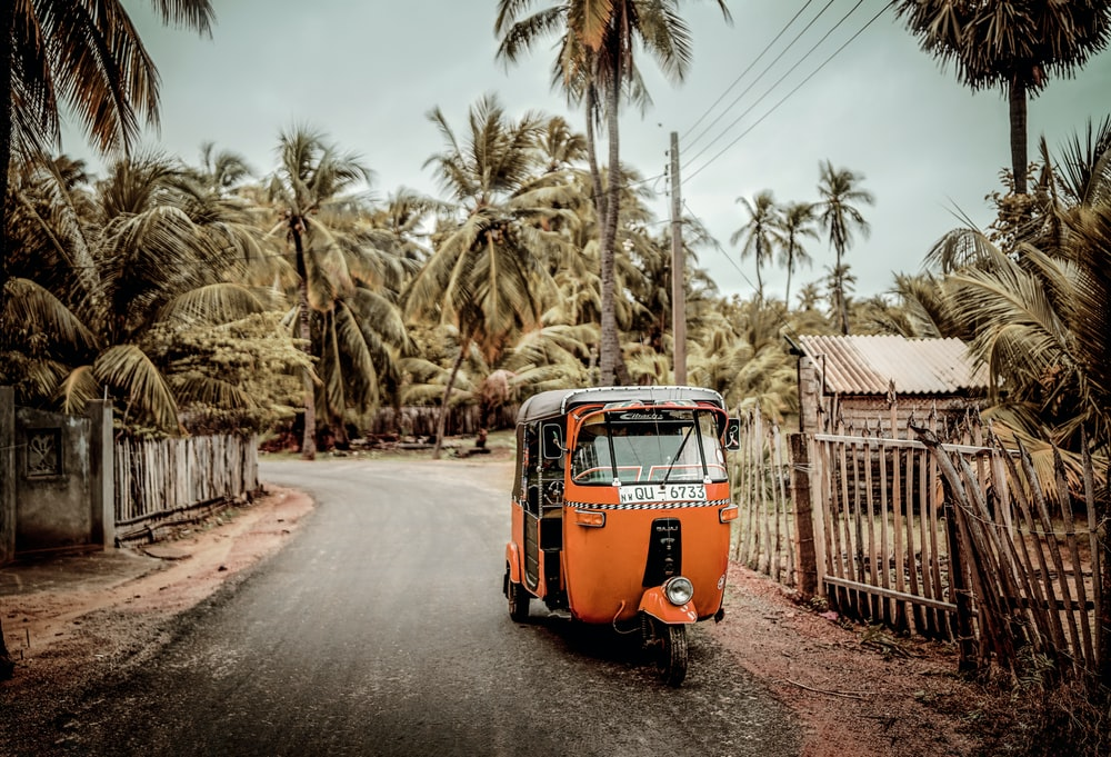 orange volkswagen t-2 van parked on the side of the road