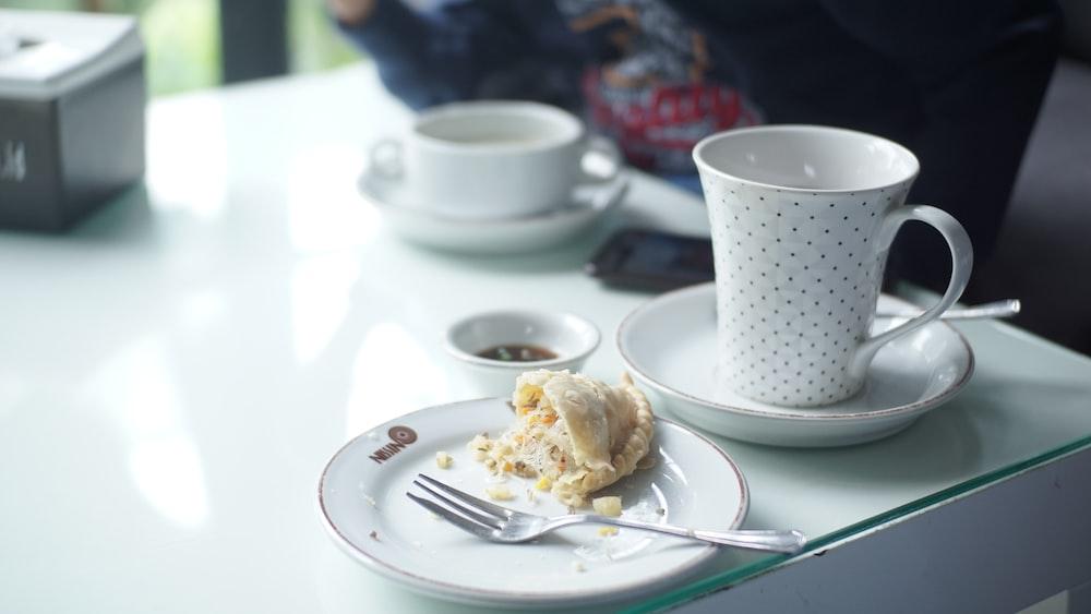 white ceramic mug on white table
