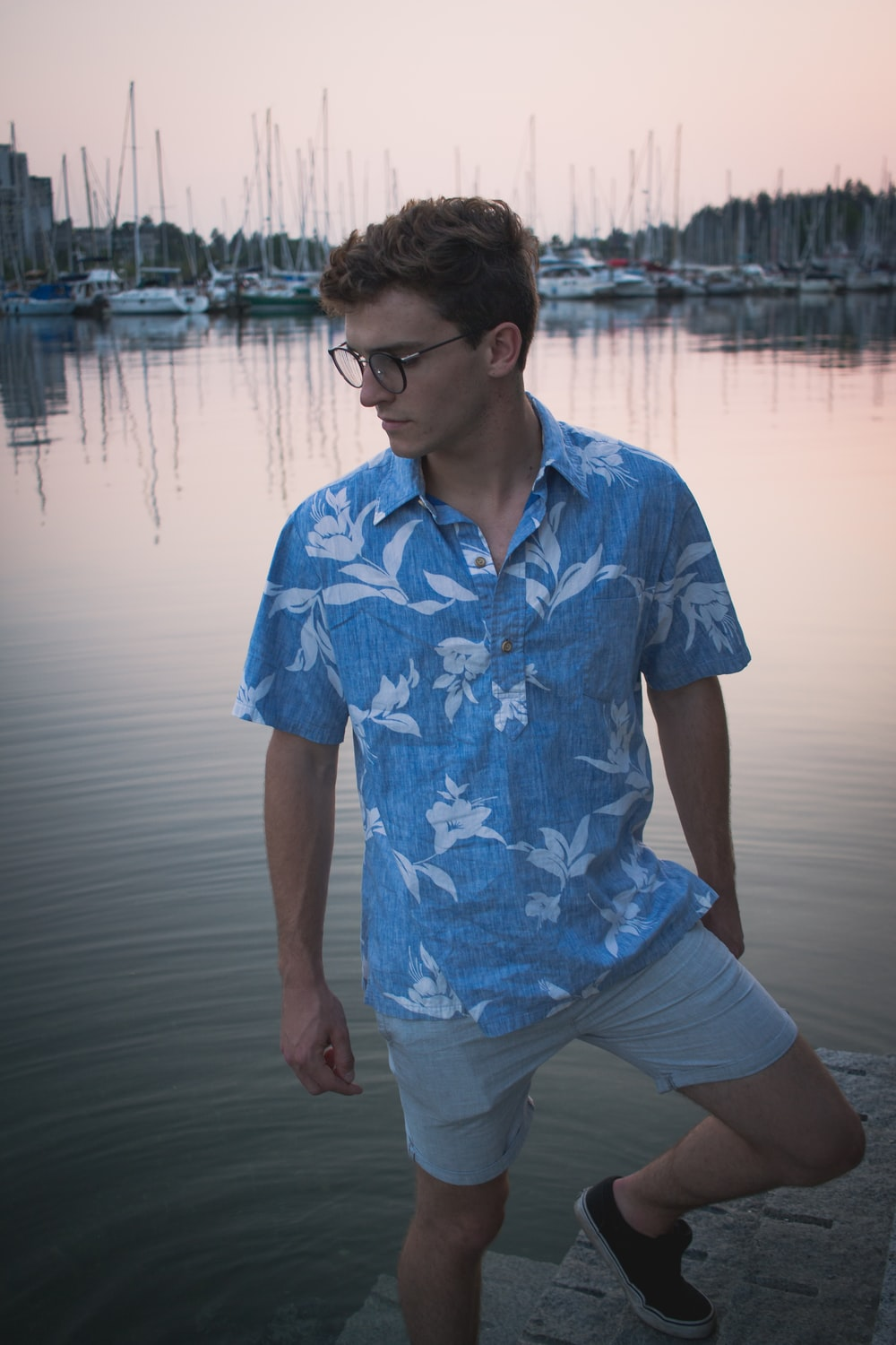 man in blue and white floral button up t-shirt standing near body of water during