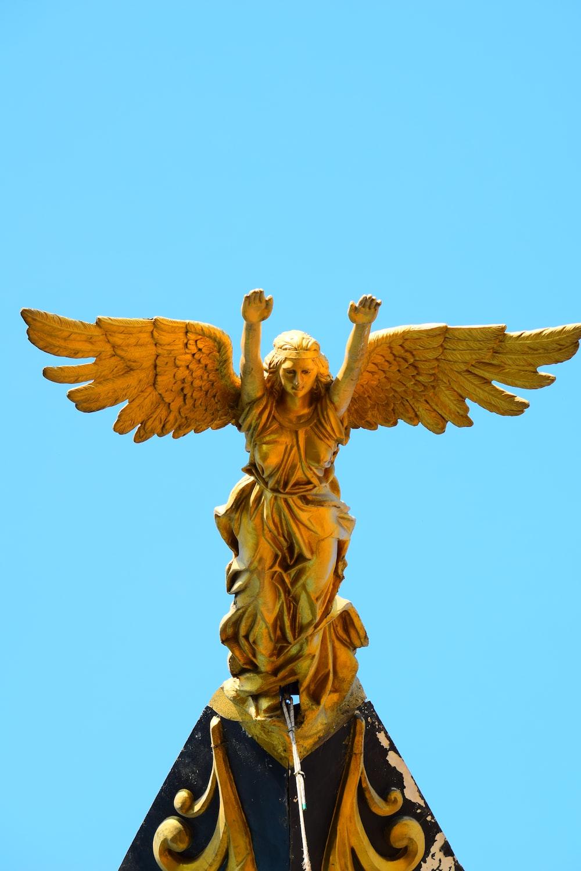 gold angel statue under blue sky during daytime