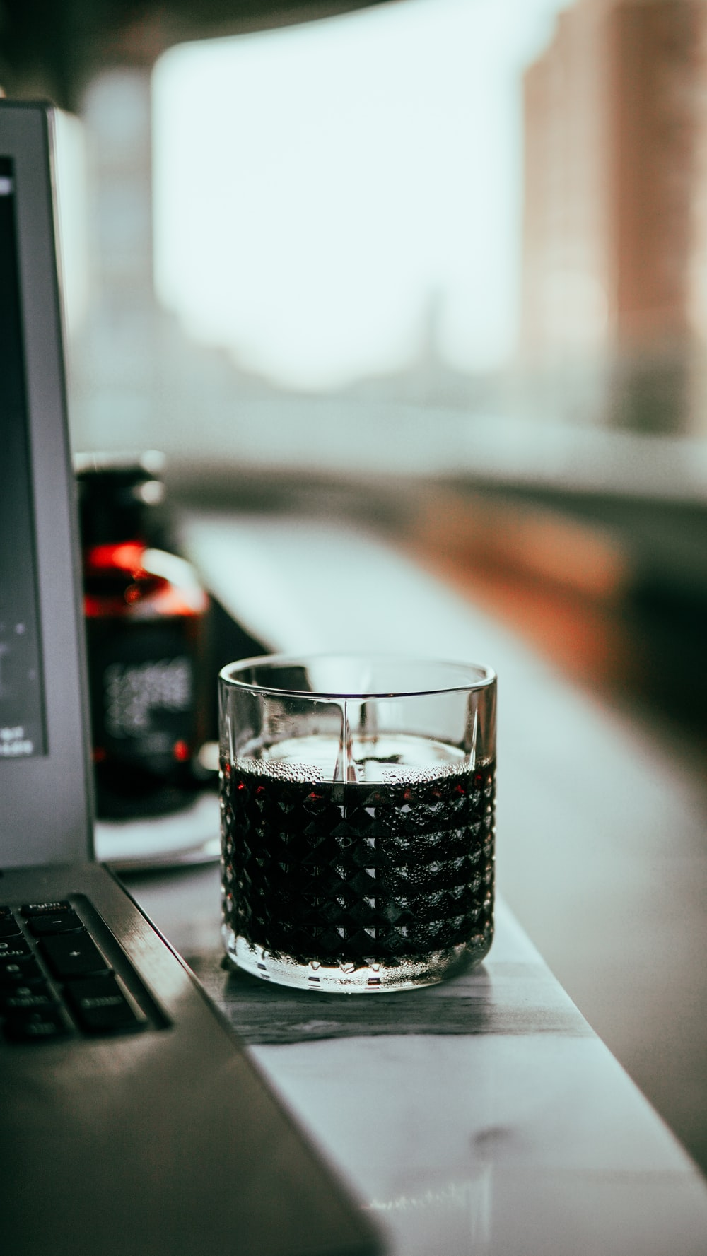 clear drinking glass on black laptop computer