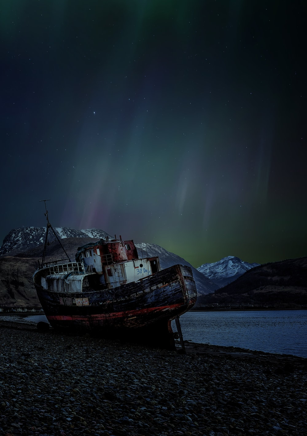 brown boat on sea shore during night time