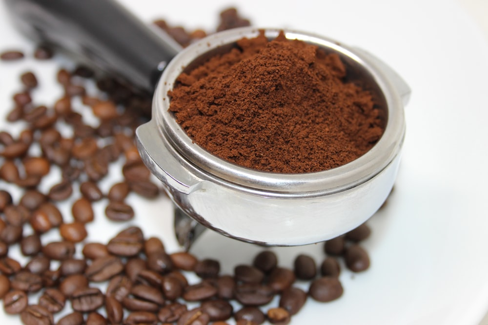 coffee beans on white ceramic mug