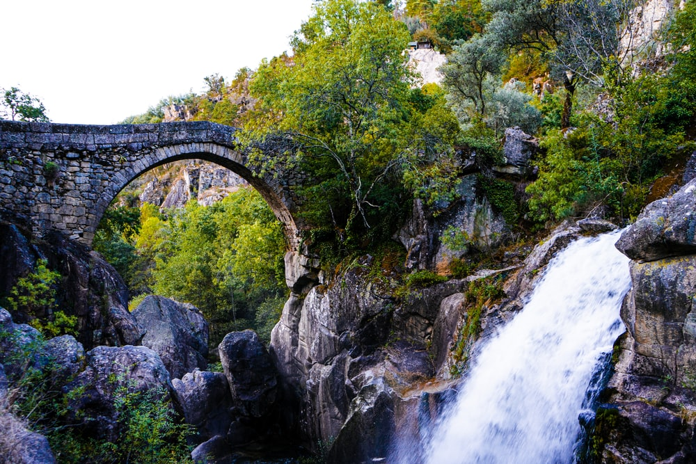 waterfalls under bridge during daytime