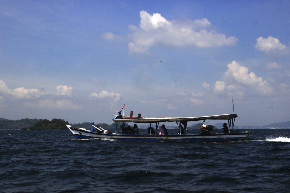 people riding on white and blue boat on sea under blue and white sky during daytime