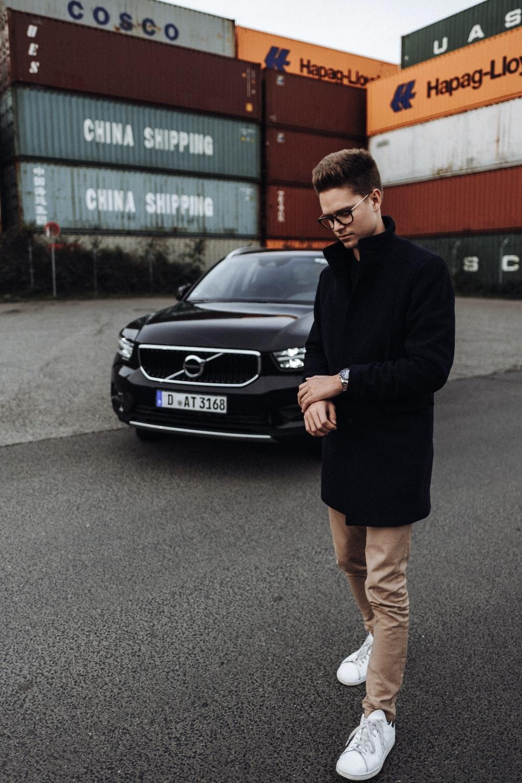 man in black blazer standing beside black mercedes benz car