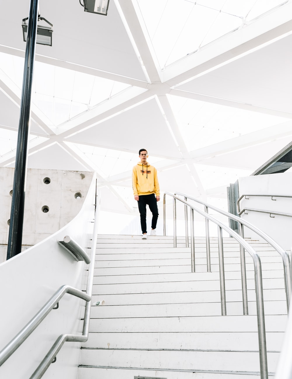 woman in yellow long sleeve shirt and black skirt walking on white staircase