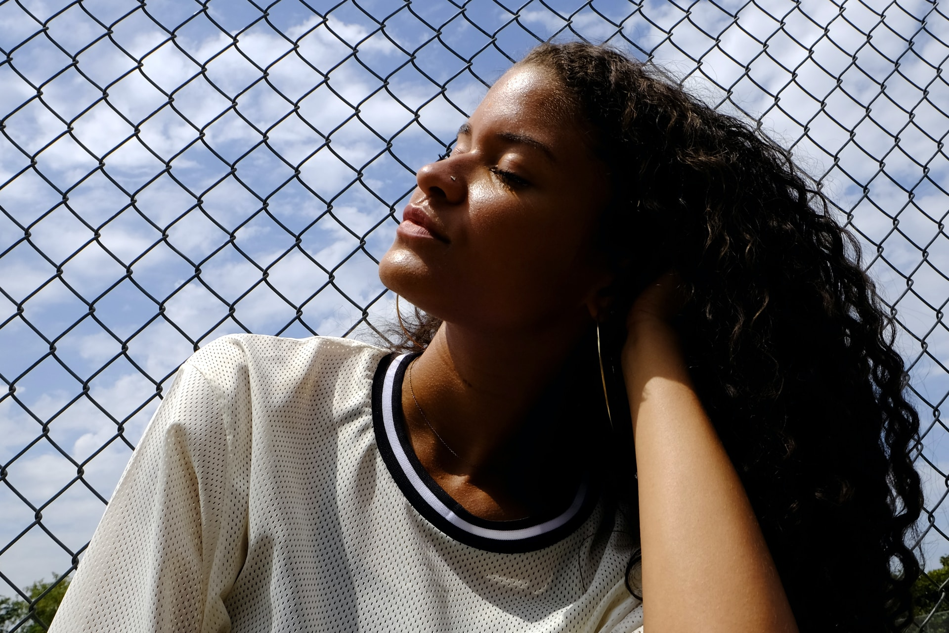 woman in white crew neck t-shirt leaning on chain link fence