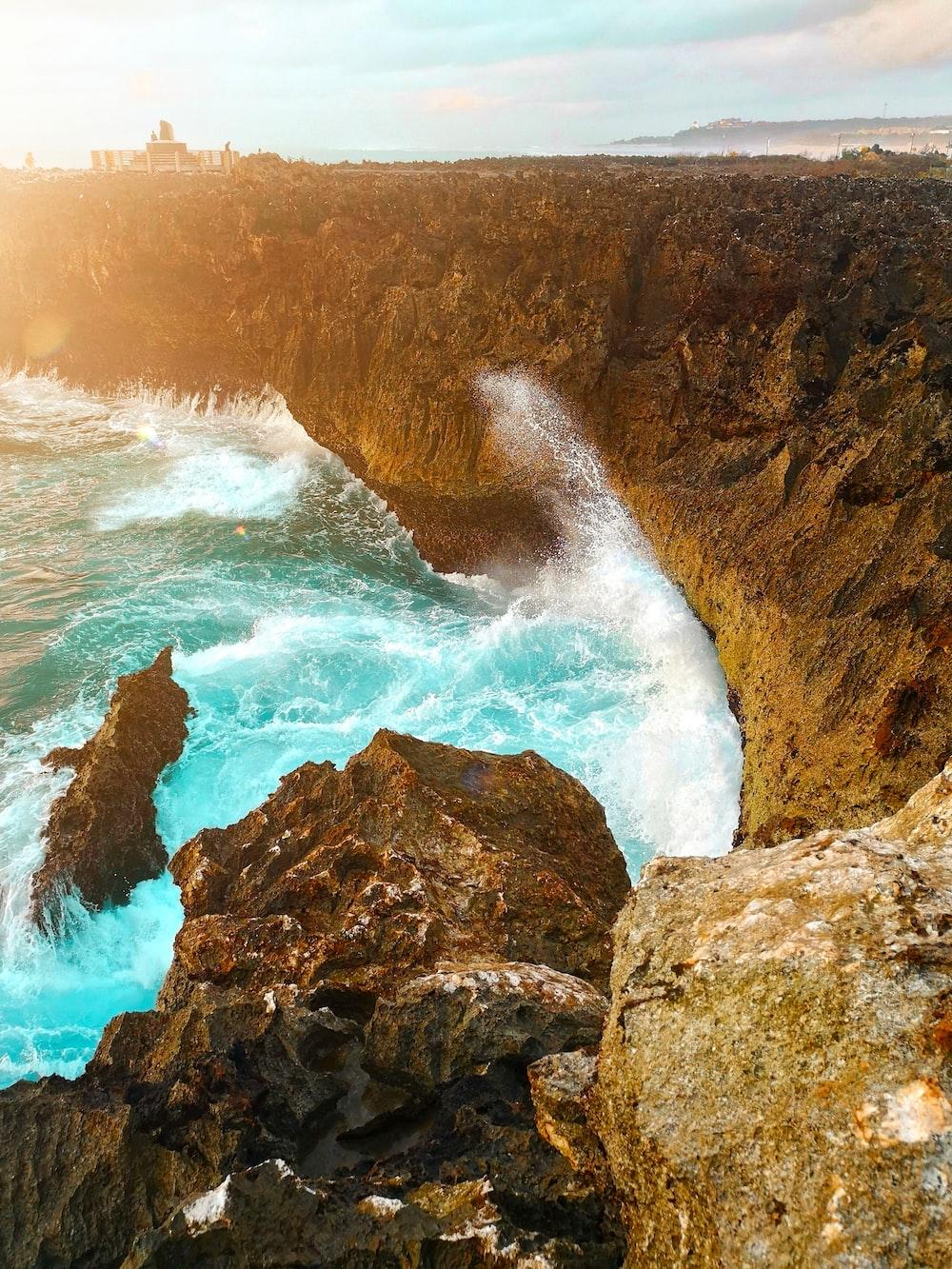water waves hitting brown rock formation during daytime