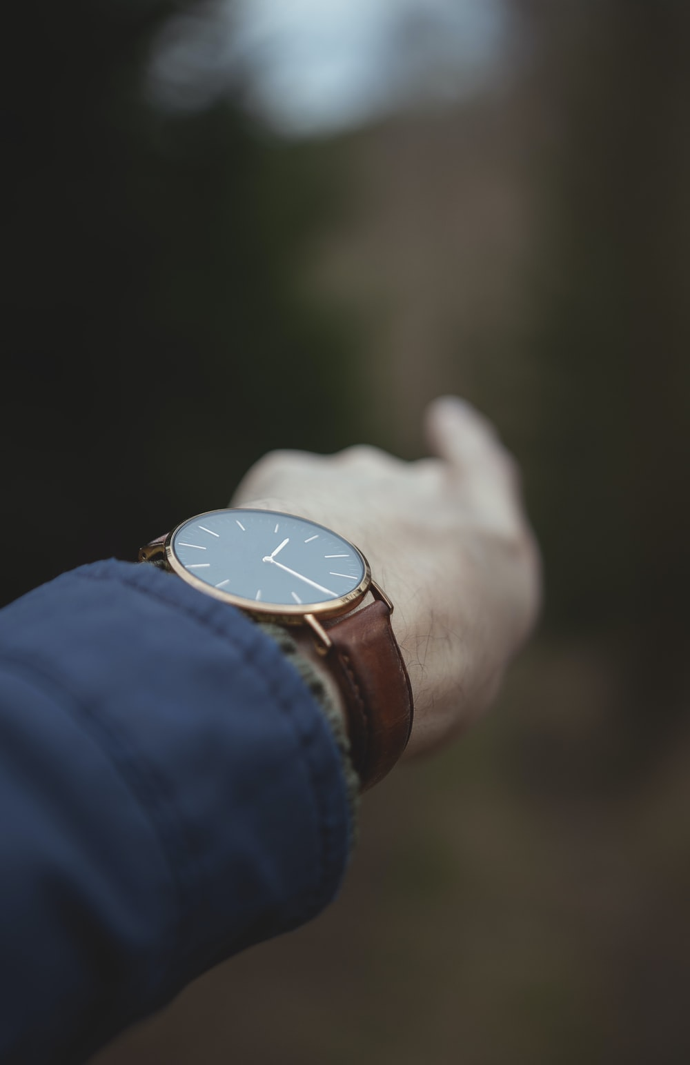 person wearing gold analog watch