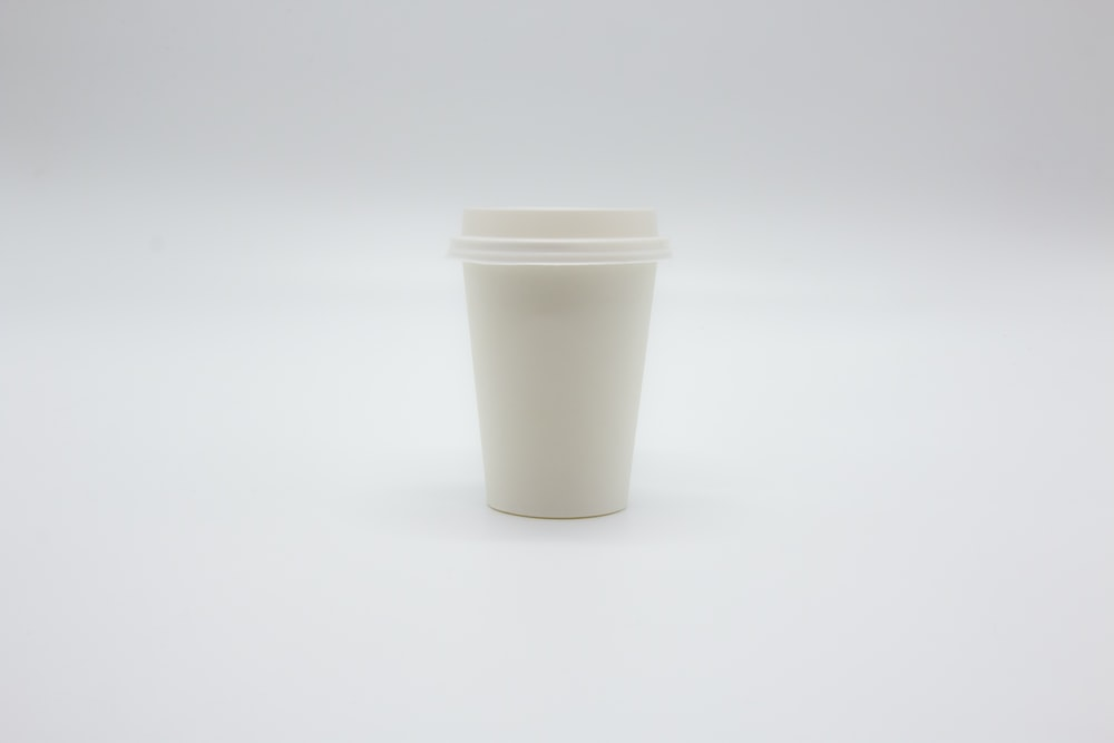 white disposable cup on white table