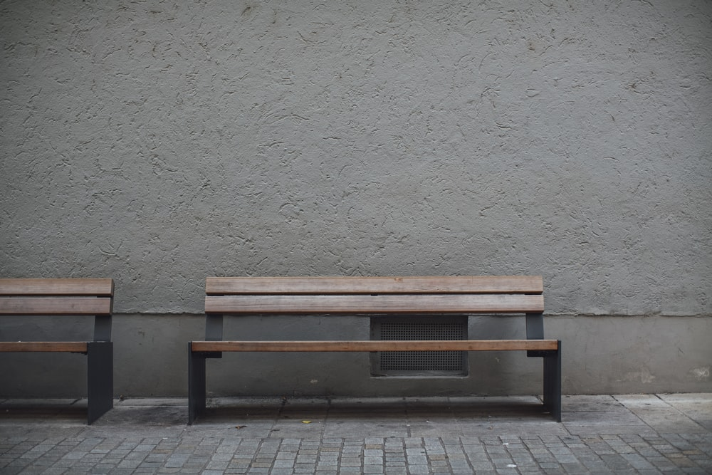 brown wooden bench beside white wall