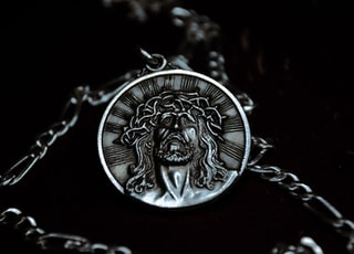 silver round pendant necklace on black surface