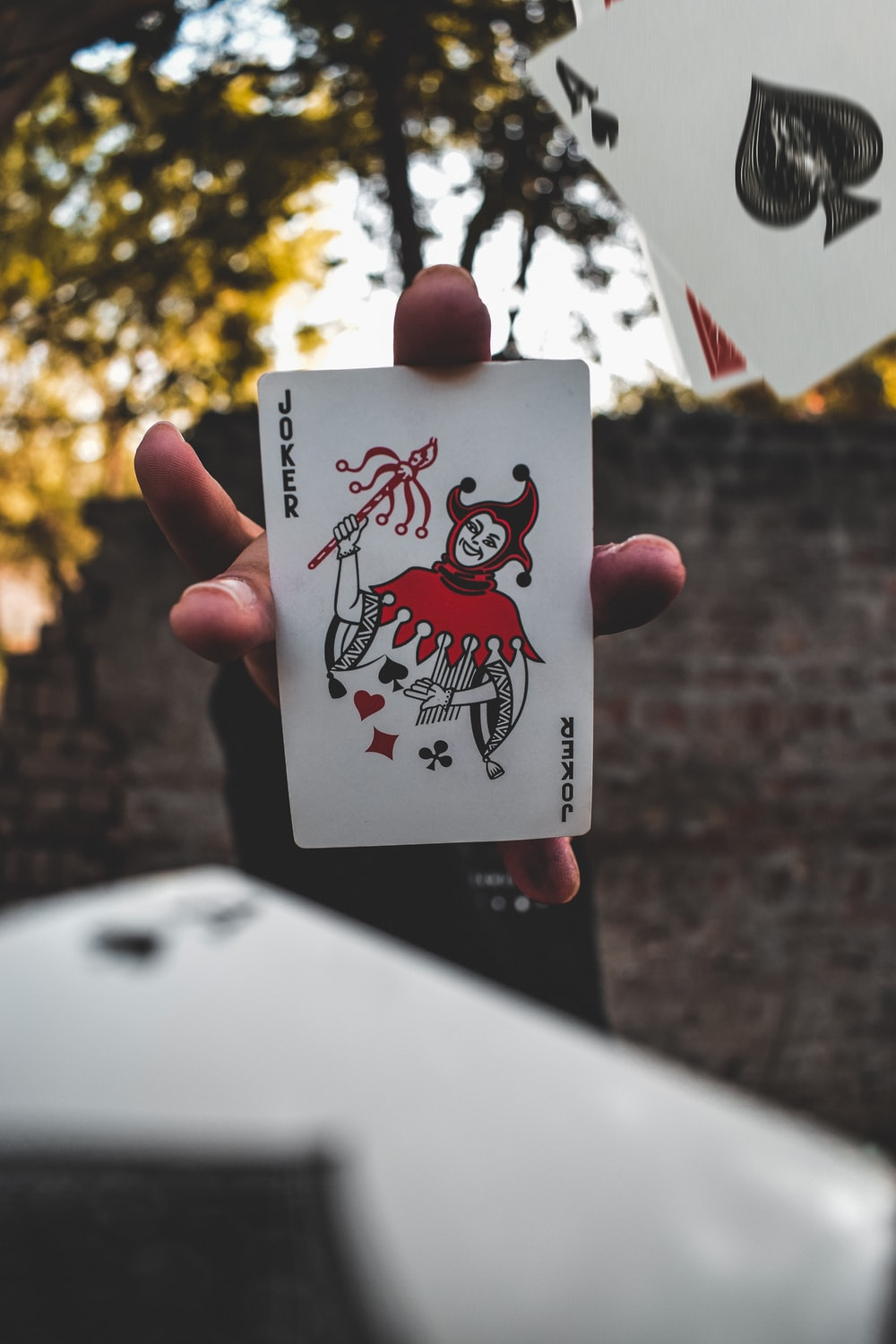 joker playing card on persons hand