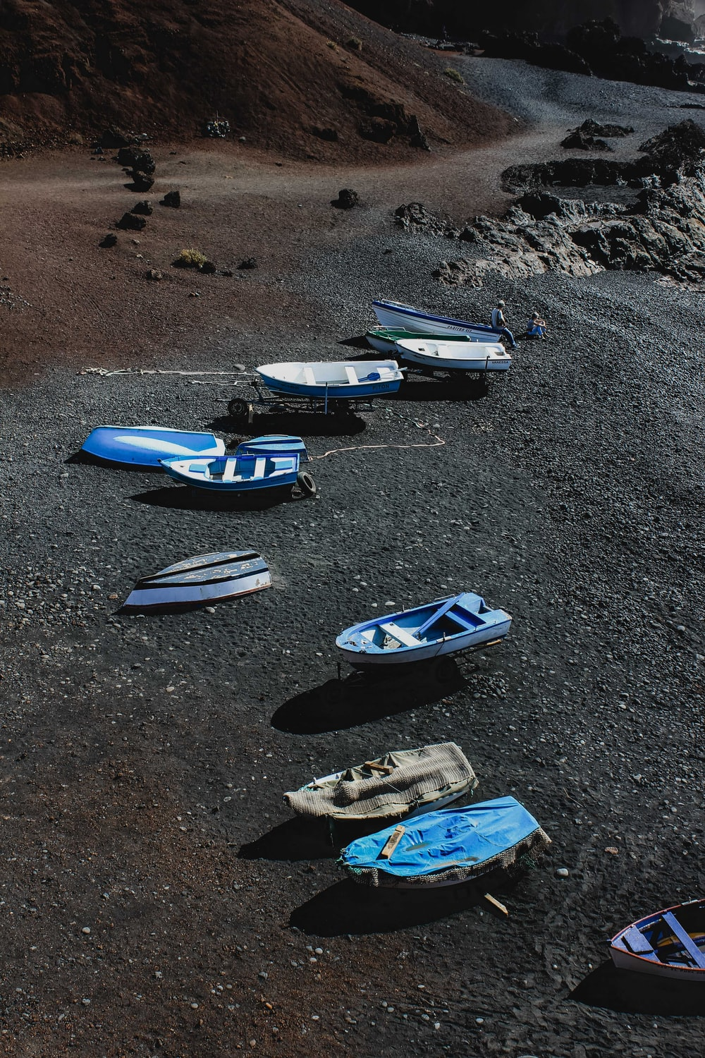 blue and white kayaks on gray sand during daytime