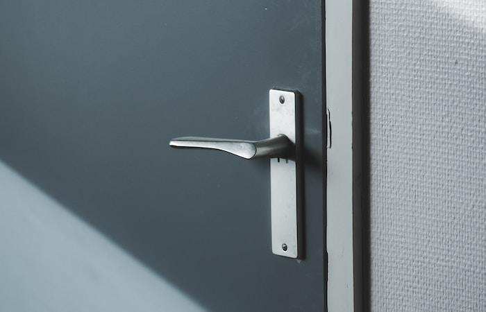 silver door lever on gray door