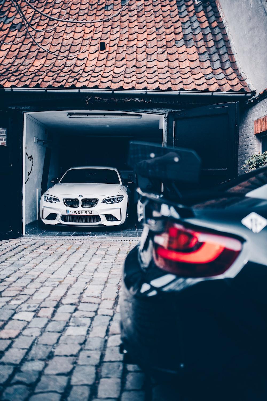 white bmw car parked beside black wooden door