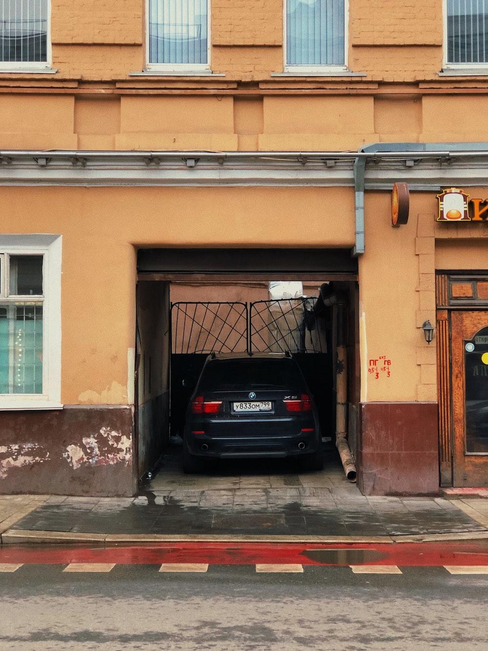 black car parked beside brown building