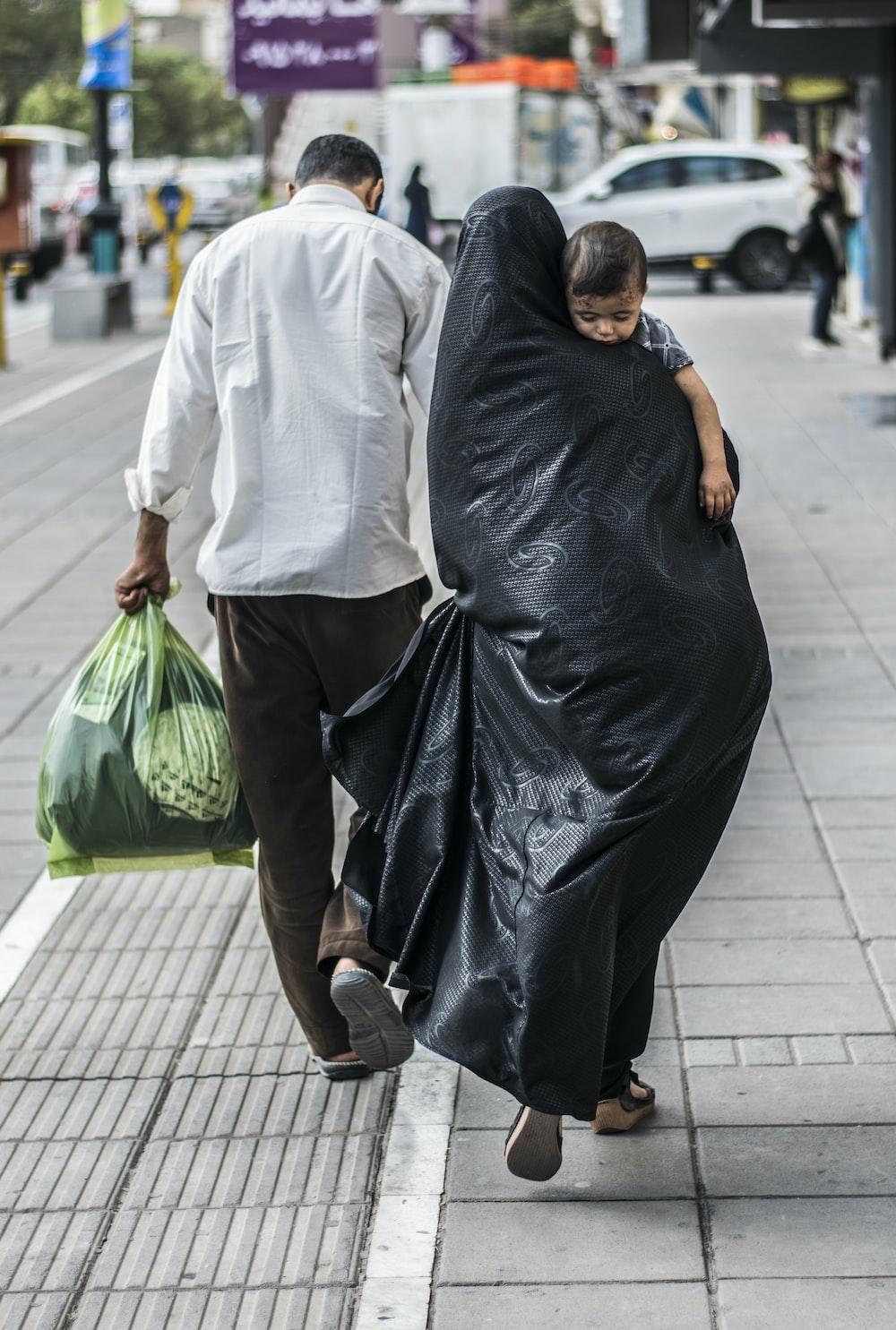 woman in black dress holding green plastic bag