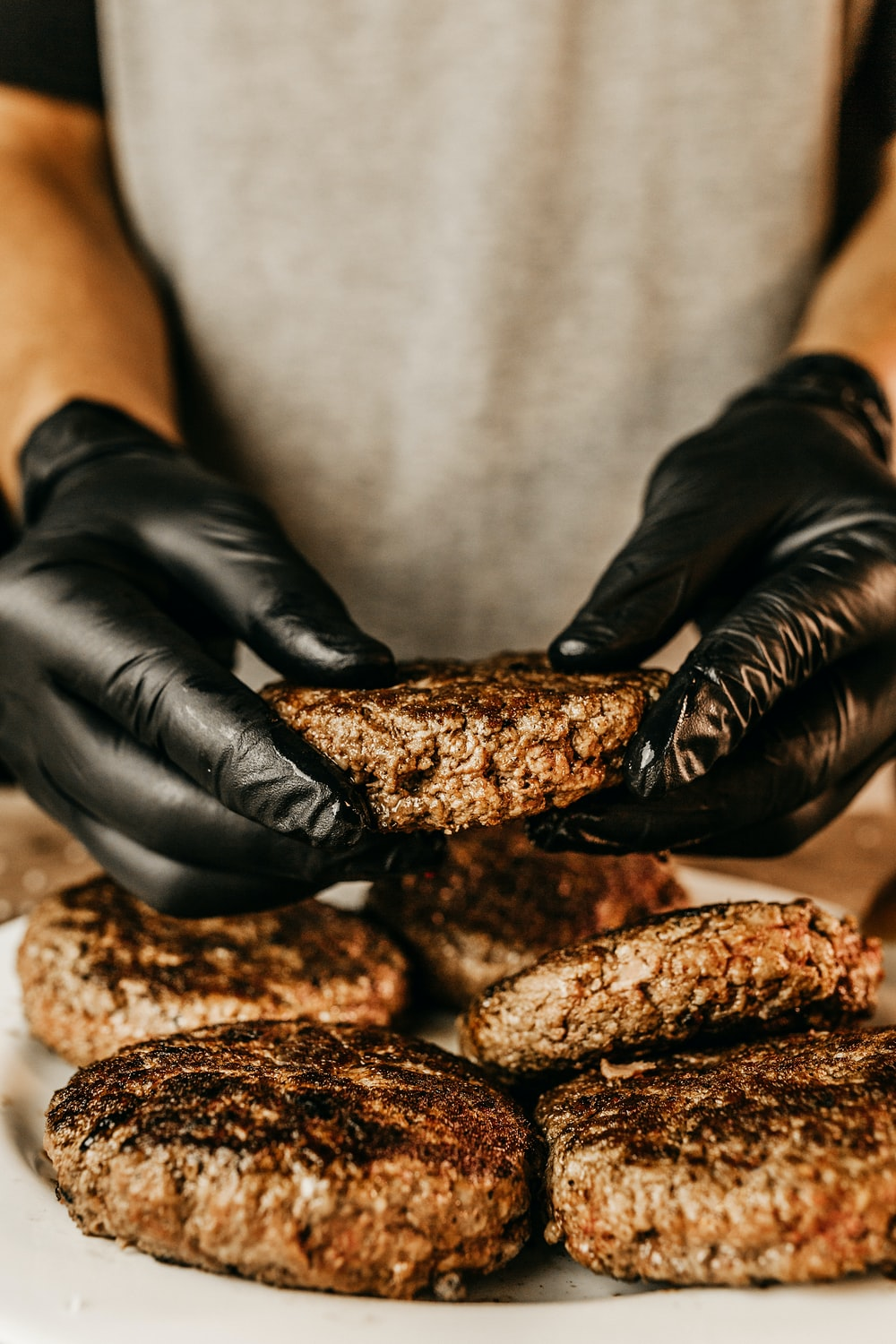 person in black leather gloves holding brown bread
