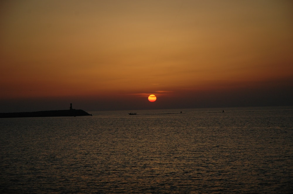 silhouette of a ship on sea during sunset