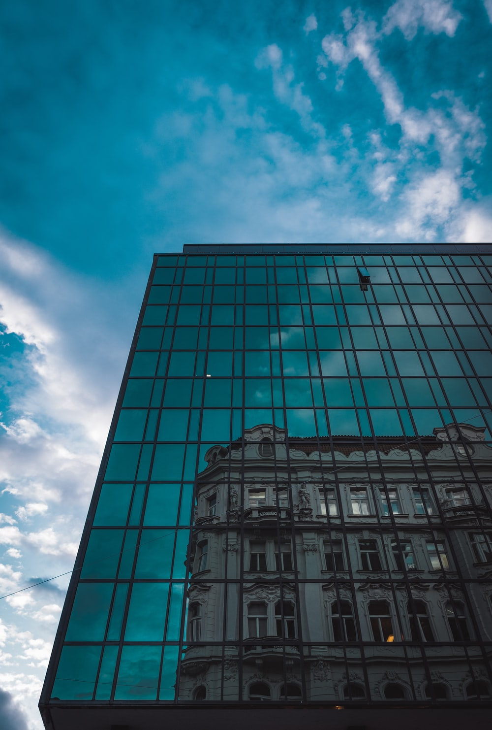 blue glass walled high rise building under blue and white cloudy sky during daytime