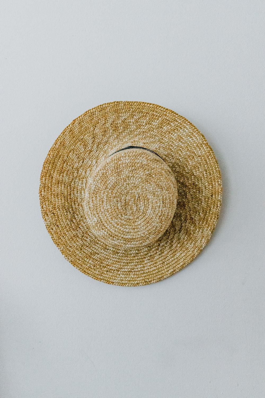 brown round hat on white surface