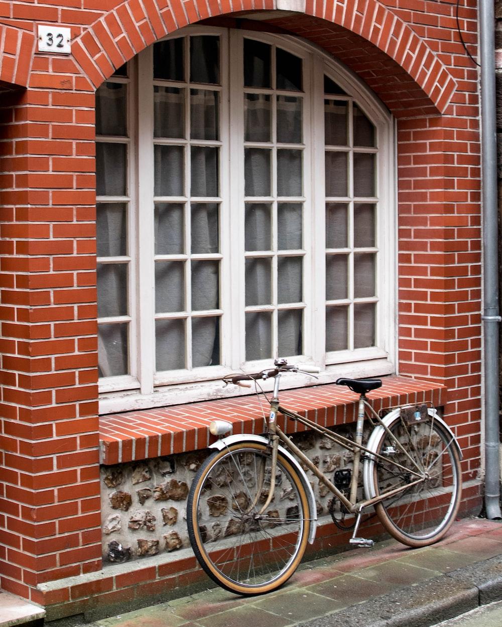 black city bike parked beside brown brick wall