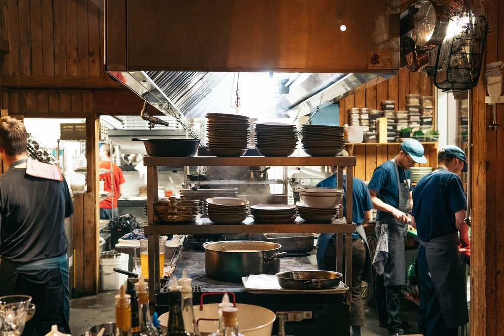 man in blue polo shirt standing near black cooking pot