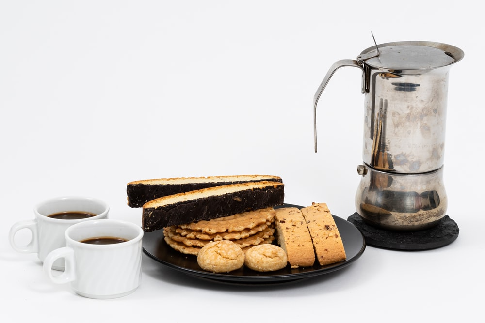 bread on brown wooden tray beside white ceramic mug