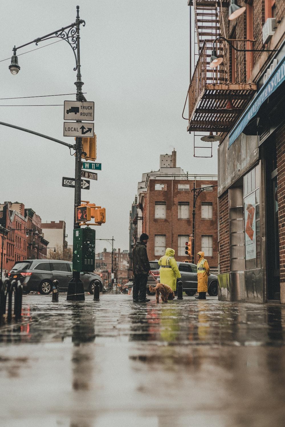 man in yellow jacket walking on street during daytime