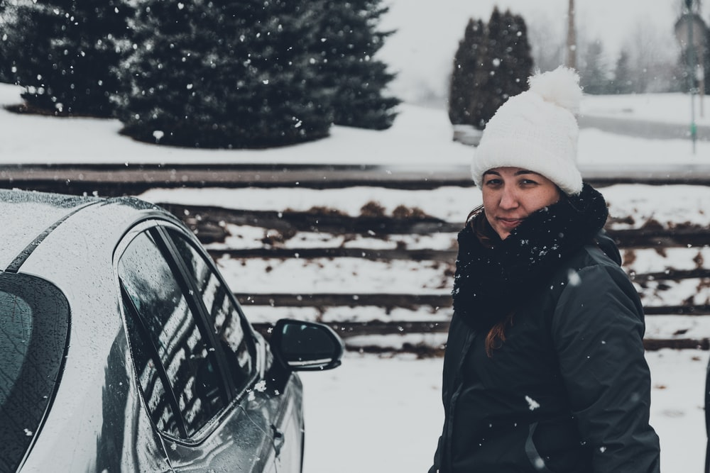 woman in black jacket and white knit cap standing on snow covered ground during daytime