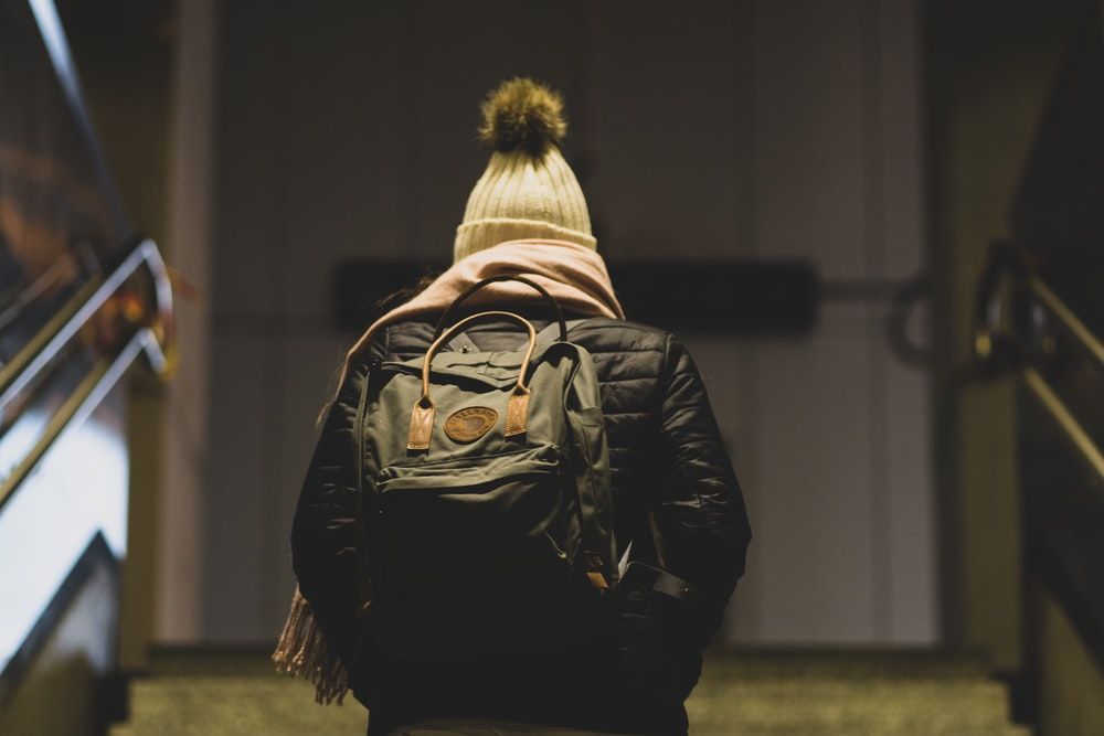 person in black leather jacket wearing brown and black backpack