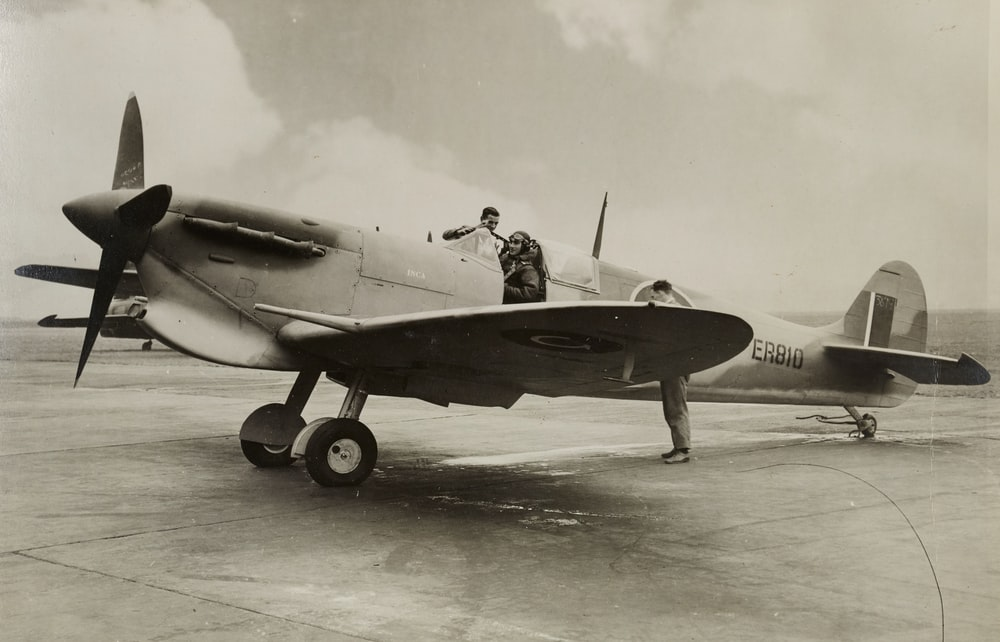 grayscale photo of man in black jacket and pants riding on jet plane