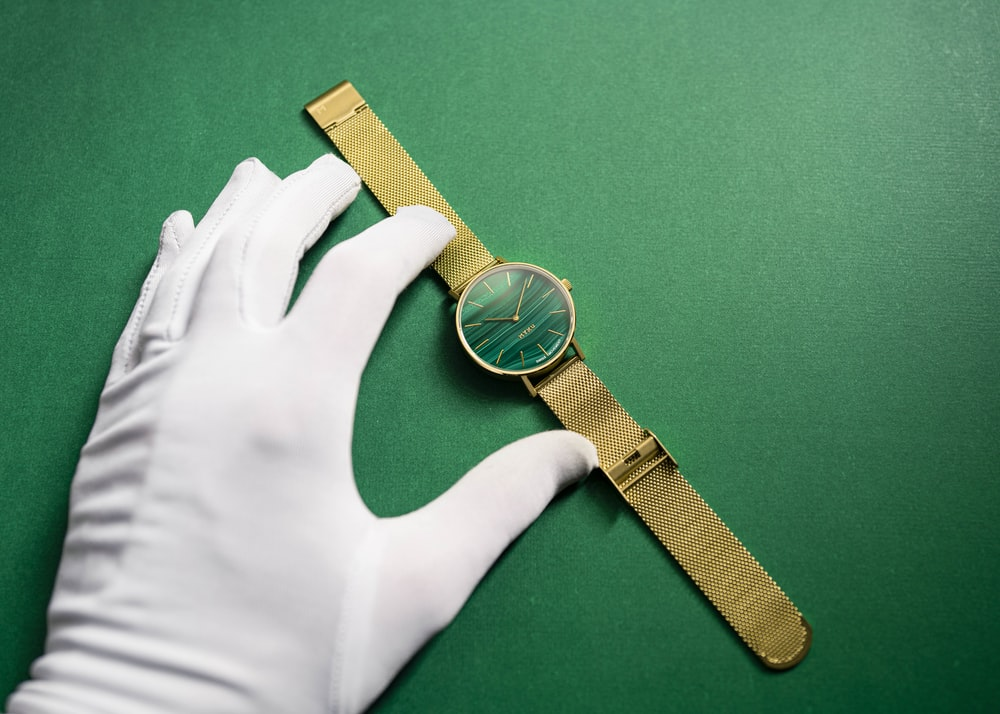 gold and silver round analog watch with brown leather strap