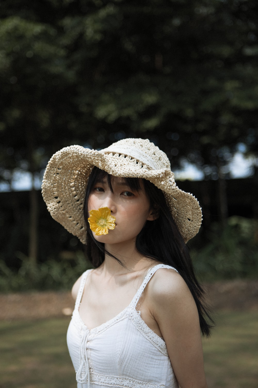 woman in white tank top wearing brown sun hat