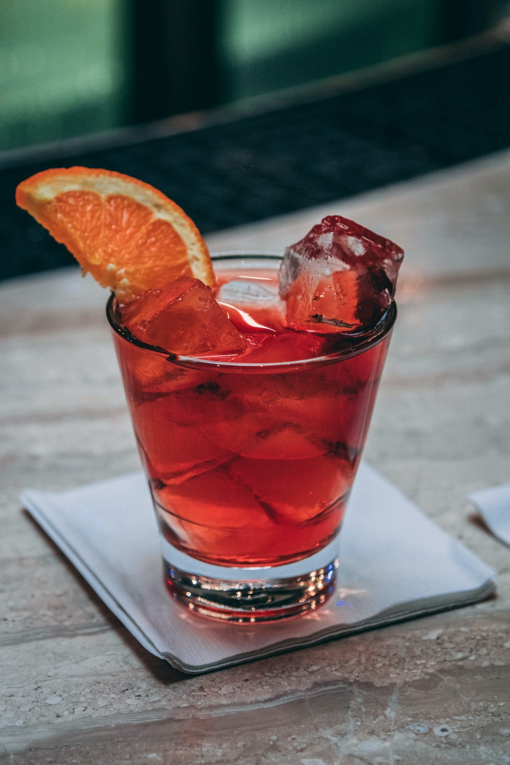clear drinking glass with red liquid and sliced orange fruit