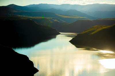green mountains beside lake during daytime lesotho teams background
