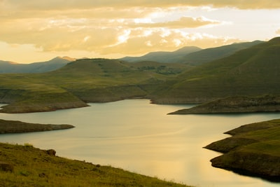 green mountains near body of water under white clouds during daytime lesotho teams background