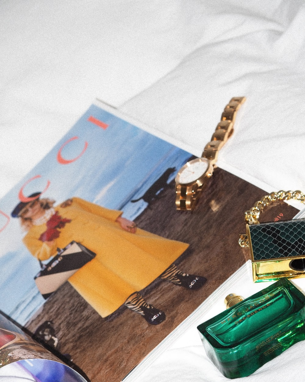 gold and green bracelet on white textile