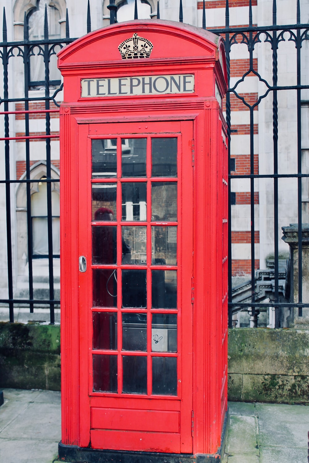 red telephone booth near building during daytime