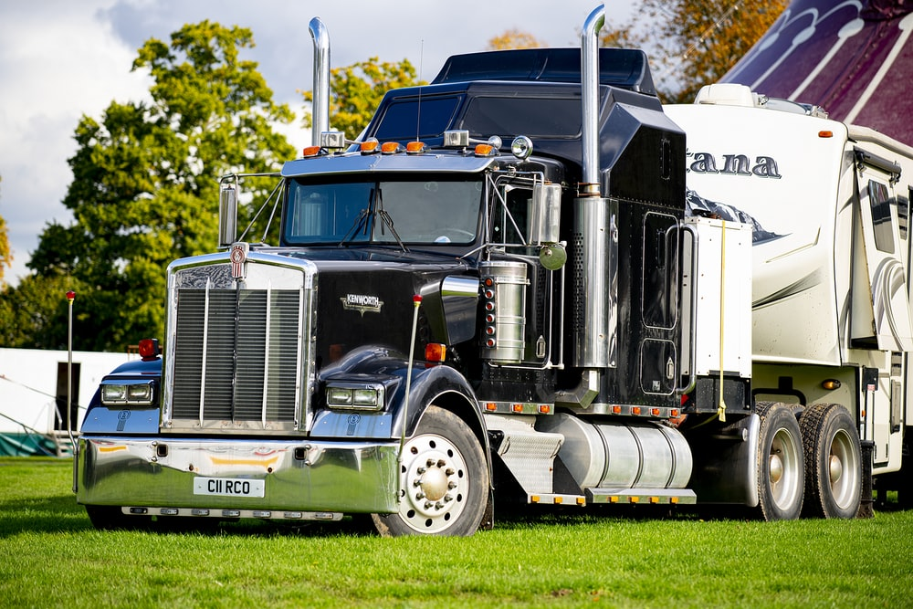 white and blue freight truck on green grass field during daytime