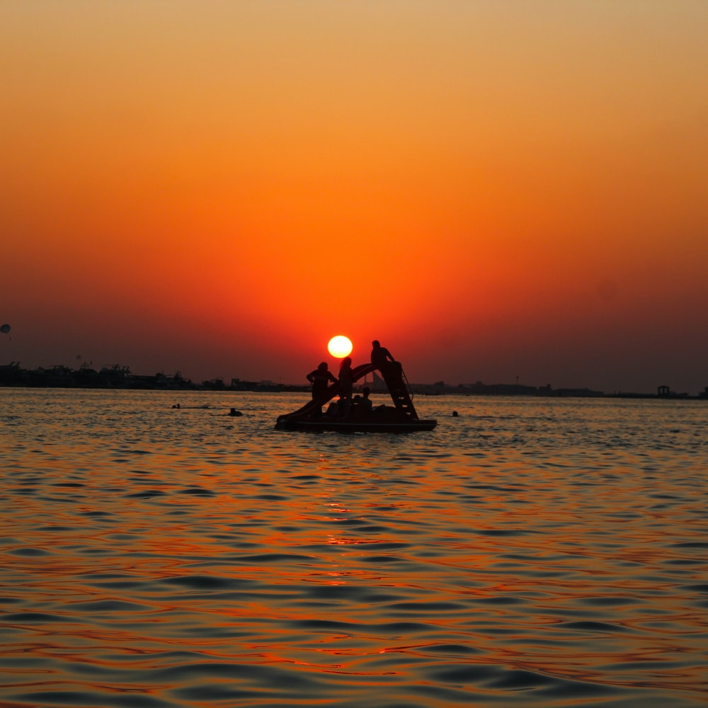 silhouette of man riding on boat during sunset