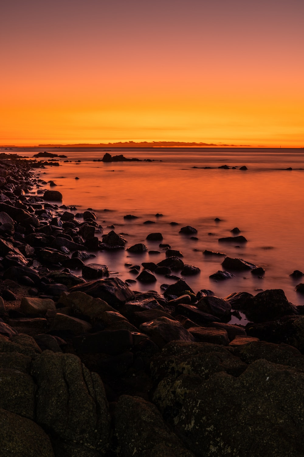 black and brown rocks on seashore during sunset