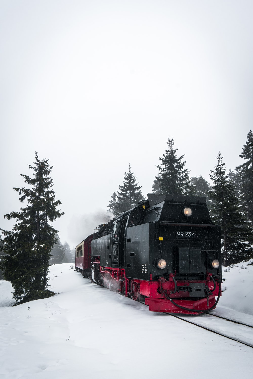 red and black train on snow covered ground during daytime