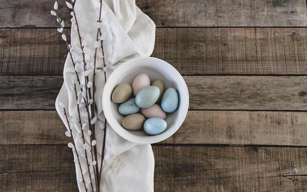 blue and green egg on white ceramic bowl