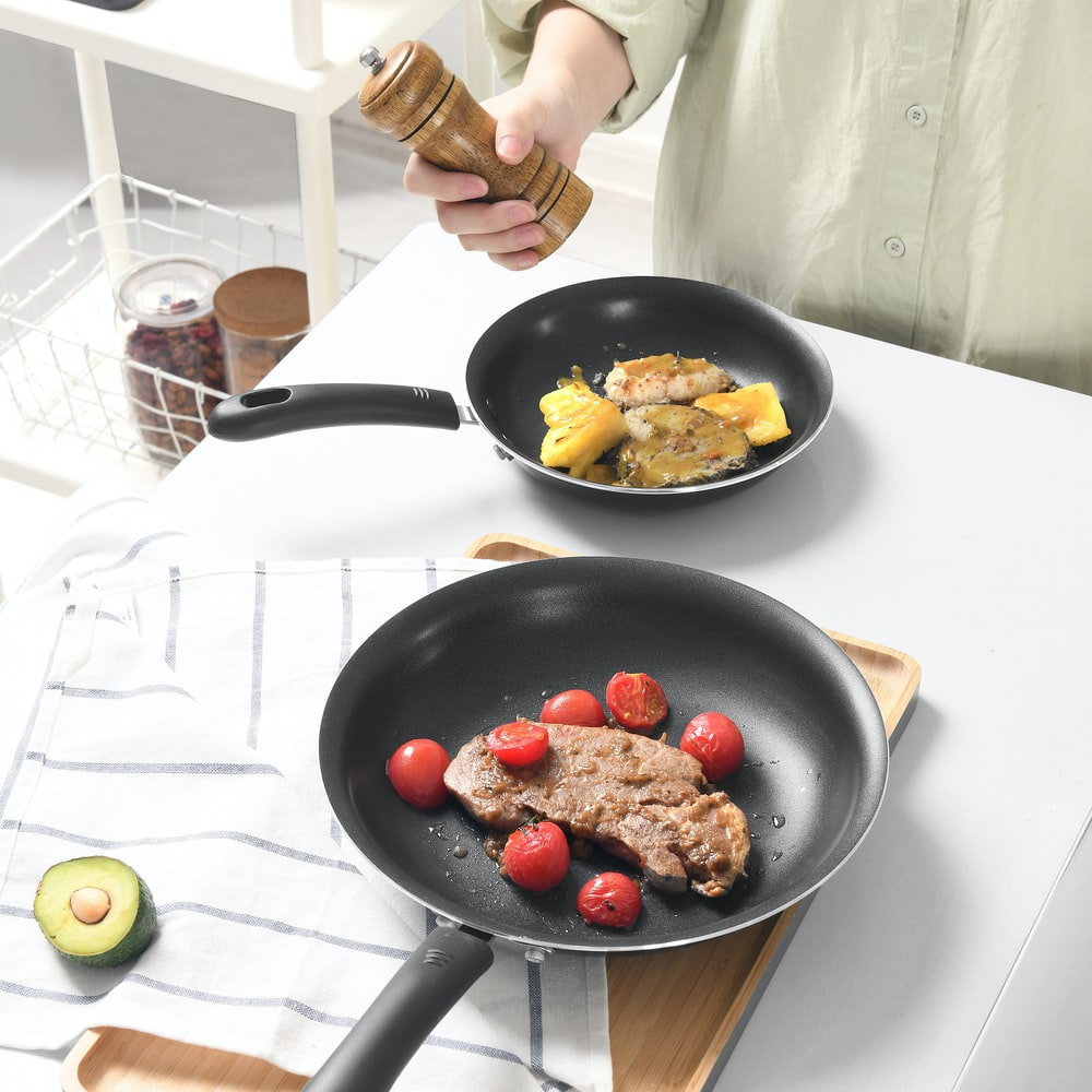 person holding black frying pan with fried food