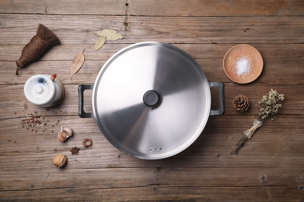 stainless steel cooking pot beside brown round fruit on brown wooden table
